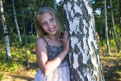 Adolescente de la muchacha en un fondo de los árboles de abedul Fotos de archivo