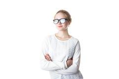 Adolescente de la muchacha en vidrios y un suéter blanco, cruzado sus brazos y sonrisas Aislado en el fondo blanco Imágenes de archivo libres de regalías