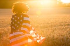 Adolescente de la muchacha envuelto en bandera de los E.E.U.U. en campo en la puesta del sol Imagen de archivo libre de regalías