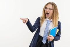 Adolescente de la muchacha, estudiante de la High School secundaria, en el fondo blanco, en uniforme escolar y señalar su dedo ín Fotografía de archivo
