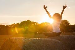 Adolescente de la muchacha de la mujer joven que se sienta en Hay Bale Celebrating Sunset Imagen de archivo libre de regalías