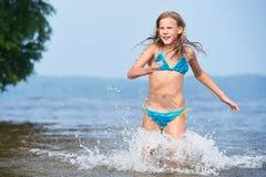 Adolescente de la muchacha que corre en el agua en el lago Foto de archivo libre de regalías