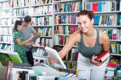 Adolescente de la muchacha que elige el libro en tienda Imagen de archivo