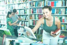 Adolescente de la muchacha que elige el libro en tienda Foto de archivo libre de regalías