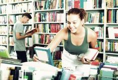 Adolescente de la muchacha que elige el libro en tienda Imágenes de archivo libres de regalías