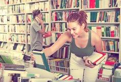 Adolescente de la muchacha que elige el libro en tienda Fotos de archivo