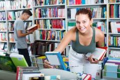 Adolescente de la muchacha que elige el libro en tienda Fotos de archivo libres de regalías