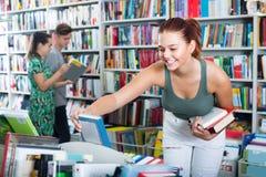 Adolescente de la muchacha que elige el libro en tienda Foto de archivo