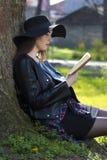 Adolescente de la muchacha que estudia en el parque Imagen de archivo libre de regalías