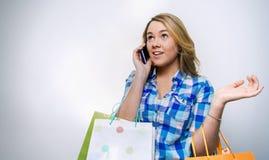 Adolescente de la muchacha que habla smartphone y sosteniéndose Foto de archivo libre de regalías