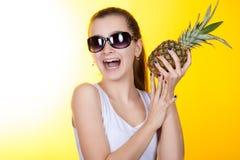 Adolescente de la muchacha que ríe y que sostiene una piña en sus manos Foto de archivo