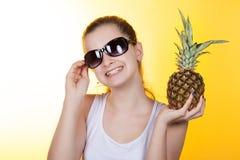 Adolescente de la muchacha que ríe y que sostiene una piña en sus manos Imagen de archivo