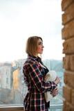 Adolescente de la muchacha que se coloca en el balcón con una almohada Fotografía de archivo