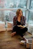 Adolescente de la muchacha que se sienta con un libro en el balcón Imagen de archivo