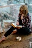 Adolescente de la muchacha que se sienta con un libro en el balcón Fotos de archivo