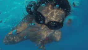 Adolescente de la muchacha subacuático en la piscina la muchacha se zambulle en la piscina debajo del agua almacen de video