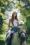 Adolescente de la muchacha y caballo blanco en un parque en un verano Imagen de archivo