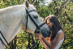 Adolescente de la muchacha y caballo blanco en un parque en un verano Foto de archivo