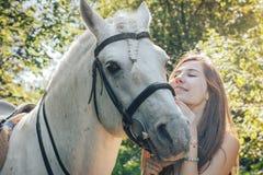 Adolescente de la muchacha y caballo blanco en un parque en un verano Fotos de archivo