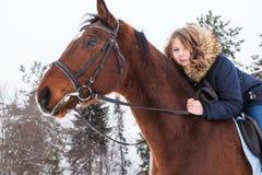 Adolescente de la muchacha y caballo grande en un invierno Fotos de archivo