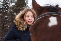 Adolescente de la muchacha y caballo grande en un invierno Imagenes de archivo