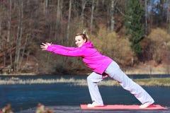 Adolescente de la mujer en el chándal que hace ejercicio en el embarcadero al aire libre Imagen de archivo libre de regalías