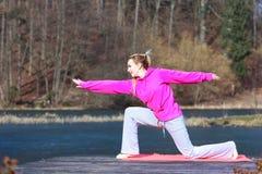 Adolescente de la mujer en el chándal que hace ejercicio en el embarcadero al aire libre Imágenes de archivo libres de regalías