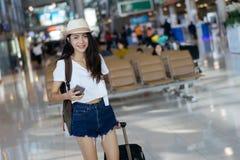 Adolescente de la mujer que usa el aeropuerto que camina del smartphone imagenes de archivo