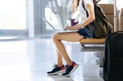 Adolescente de la mujer que usa el ordenador portátil en el aeropuerto fotos de archivo