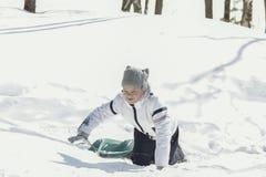 Adolescente de la niña en un bosque soleado del invierno con el trineo Foto de archivo