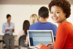 Adolescente de la raza mixta que usa el ordenador portátil en clase Imagen de archivo libre de regalías