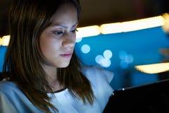 Adolescente de Latina que usa el Tablet PC interior en la noche Imagen de archivo