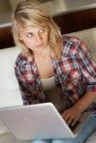 Adolescente de mirada culpable que usa la computadora portátil Fotos de archivo