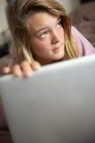 Adolescente de mirada culpable que usa la computadora portátil en el país Fotos de archivo