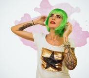 Adolescente de moda con el pelo verde que escucha la música en los auriculares Foto de archivo libre de regalías