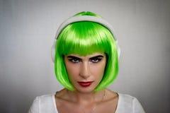 Adolescente de moda con el pelo verde que escucha la música en los auriculares Mirada de la cámara, mirada malvada Primer Imagen de archivo