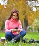Adolescente de moda joven con smartphone, la cámara y el café para llevar en parque en la sentada y la sonrisa del otoño Imagenes de archivo