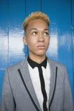 Adolescente de moda que mira lejos contra el revestimiento de madera de madera Foto de archivo libre de regalías