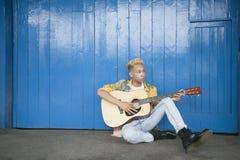 Adolescente de moda que toca la guitarra como él se sienta contra la pared artesonada madera Fotografía de archivo
