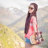 Adolescente de mode avec la planche à roulettes de longboard à la montagne Image libre de droits