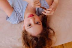 Adolescente de olhos azuis que encontra-se na cama ao ter o tempo livre imagem de stock