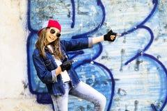 Adolescente de pelo rubio joven lindo de la muchacha en una camisa de la gorra de béisbol y del dril de algodón en un fondo de la Fotos de archivo