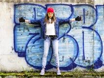 Adolescente de pelo rubio joven lindo de la muchacha en una camisa de la gorra de béisbol y del dril de algodón en un fondo de la Imágenes de archivo libres de regalías