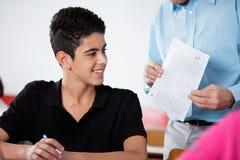 Adolescente de profesor Holding Paper With en el escritorio Imagen de archivo
