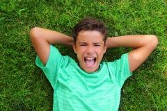 Adolescente de risa del muchacho que pone la hierba verde Imagen de archivo libre de regalías