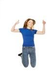 Adolescente de salto con los pulgares para arriba Fotos de archivo