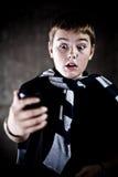 Adolescente de Scarry que mira su teléfono móvil Fotografía de archivo libre de regalías