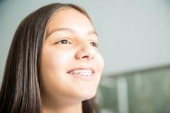 Adolescente de sorriso com as cintas na clínica dental fotografia de stock