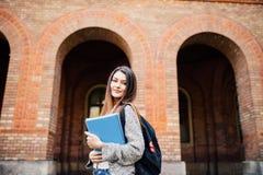 Adolescente de sorriso com dobradores e saco no fundo de universidade imagem de stock