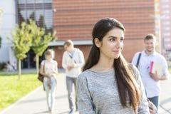 Adolescente de sorriso que olha afastado ao andar com os amigos no campus universitário foto de stock